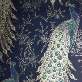 A navy blue wallpaper with peacocks and flowers all over the surface lined in with gold.